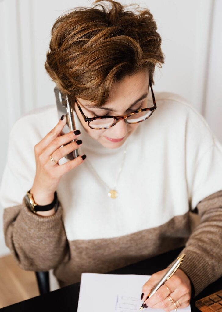 Female on the phone, taking notes