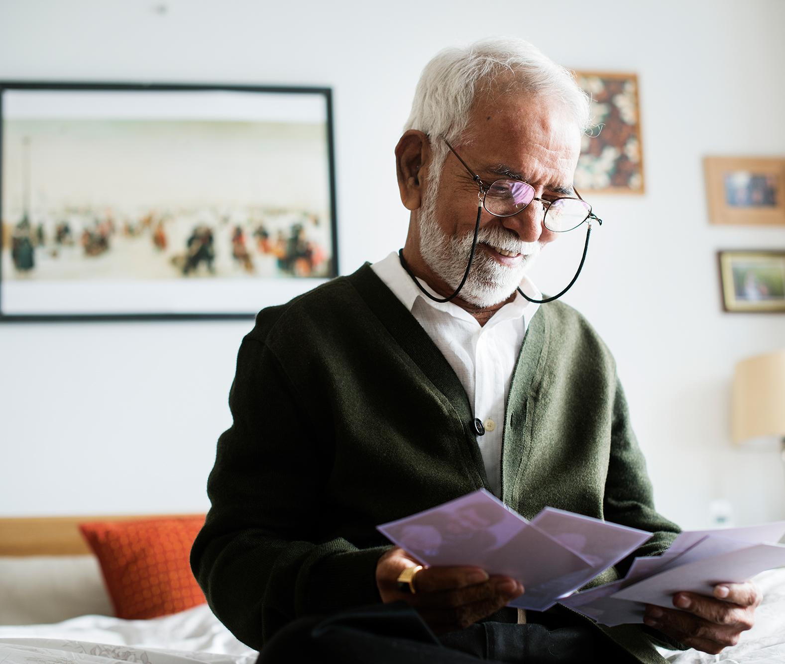 elderly man looking at photos at home