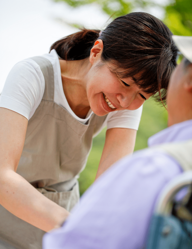 Asian woman smiling and helping another person in the park