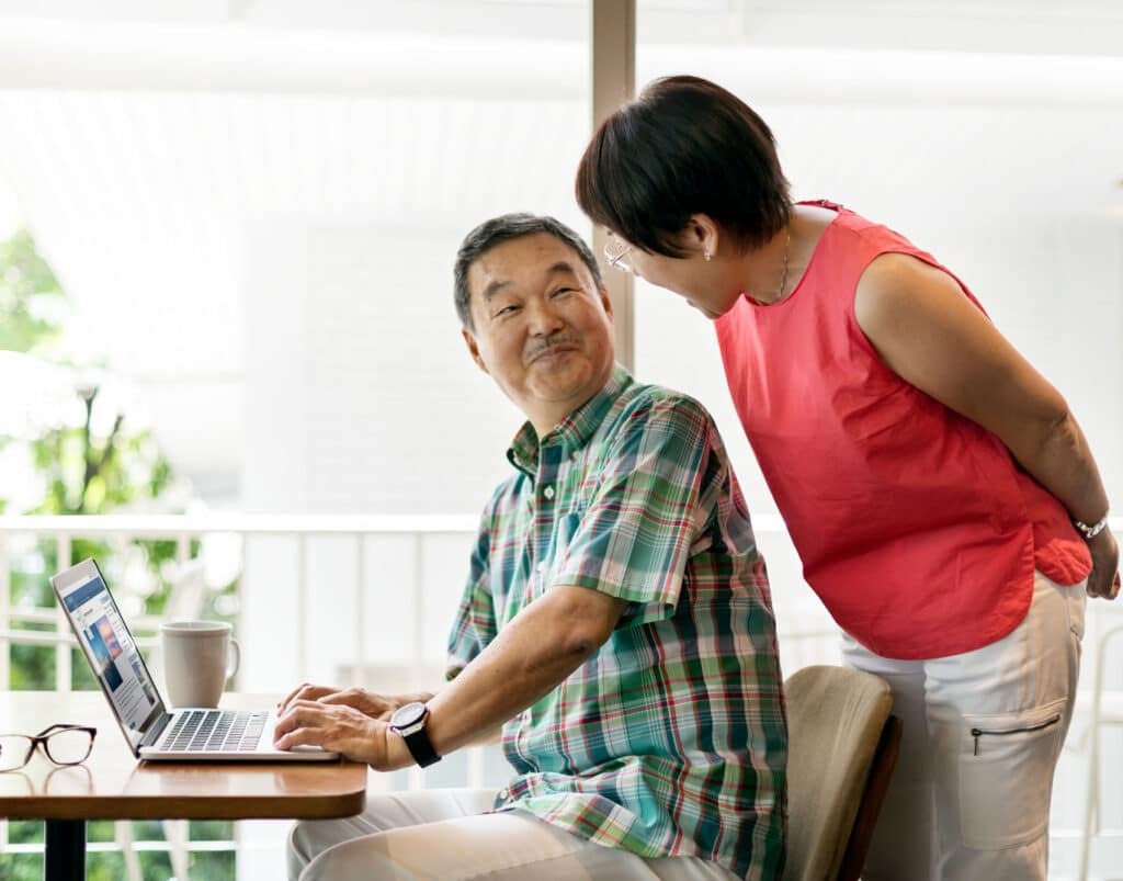 Asian couple in the kitchen with husband in front of the computer, looking back at his wife